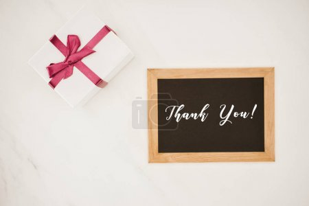 top view of blackboard in frame with THANK YOU lettering and gift box isolated on white