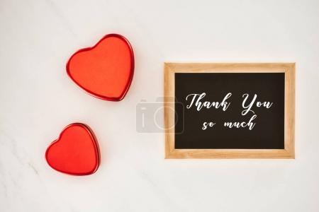 Photo pour Vue de dessus du tableau noir dans le cadre avec MERCI vous lettrage tellement mUCH avec coeur en forme isolé sur blanc - image libre de droit