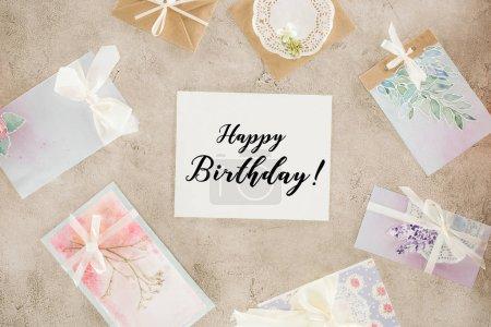 vue de dessus du papier avec l'inscription joyeux anniversaire entourée de cartes de voeux sur la surface du béton