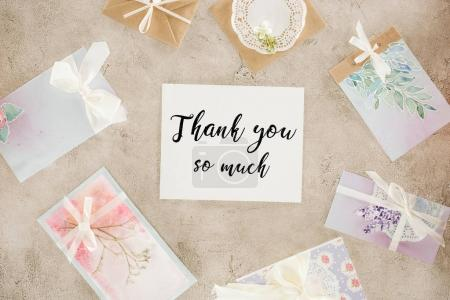 Photo pour Vue du dessus du papier avec lettrage de remerciement entouré de cartes de vœux sur la surface en béton - image libre de droit
