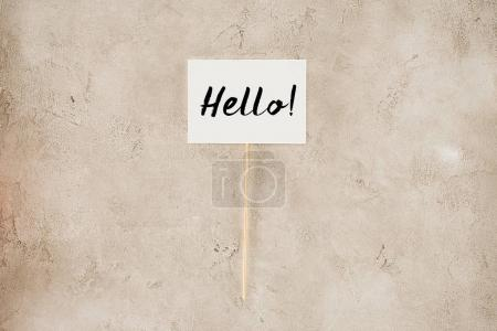 top view of hello lettering on placard on concrete surface