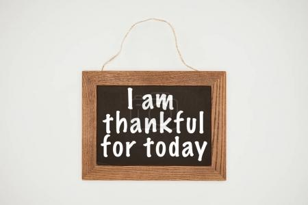 i am thankful today lettering on chalkboard with wooden frame and thread isolated on white