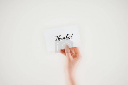 cropped shot of woman holding paper with thanks lettering isolated on white