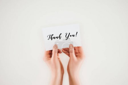 cropped shot of woman holding paper with thank you lettering in hands isolated on white