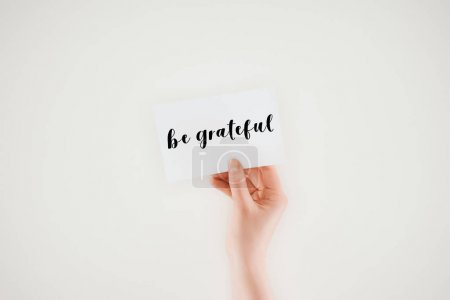 cropped shot of woman holding paper with be grateful lettering isolated on white