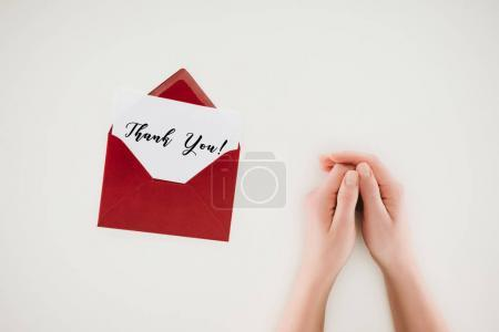 Photo for Cropped shot of woman holding hands near opened red envelope with thank you lettering on paper isolated on white - Royalty Free Image