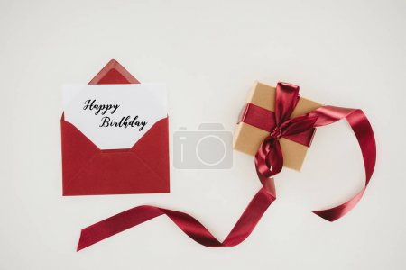 top view of red envelope with happy birthday lettering on paper and gift box isolated on white