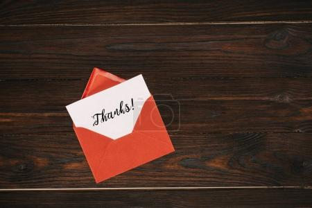 Photo for Top view of red envelope with thanks lettering on paper on wooden table - Royalty Free Image