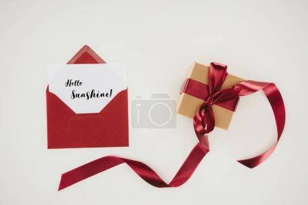 top view of red envelope with hello sunshine lettering on paper and gift box isolated on white