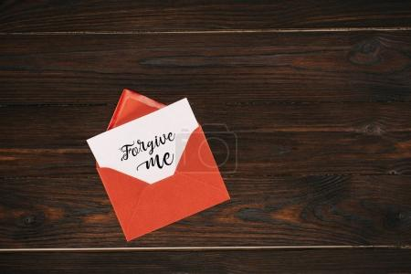 top view of red envelope with forgive me lettering on paper on wooden table