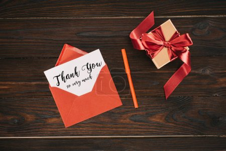 top view of red envelope with thank you so very much lettering on paper and gift box on wooden table
