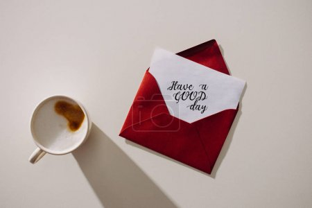 top view of red envelope with have a good day lettering lettering on paper paper and cup of coffee