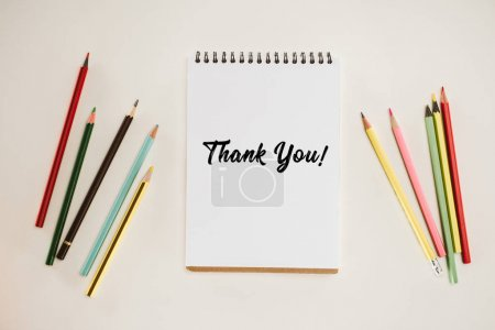 top view of notepad with thank you lettering and colorful pencils isolated on white