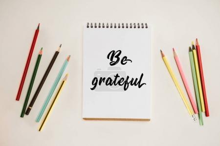 Photo for Top view of notepad with be grateful lettering and colorful pencils isolated on white - Royalty Free Image