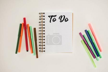 top view of notepad with blank to do list and colorful markers isolated on white