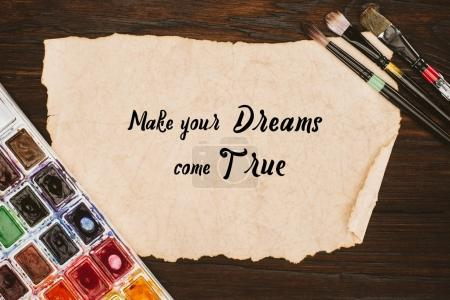top view of aged paper with make your dreams come true lettering and painting supplies on wooden table