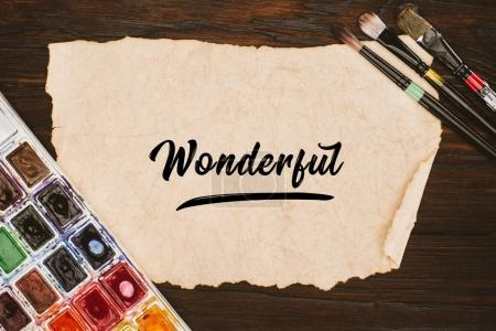 top view of aged paper with wonderful lettering and painting supplies on wooden table