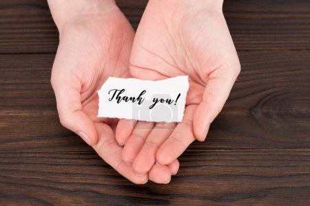 Photo for Cropped shot of woman holding paper with thank you lettering over wooden table - Royalty Free Image