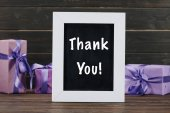 thank you lettering on chalkboard in frame with gift boxes against wooden wall