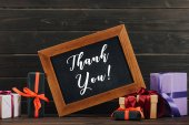 thank you lettering on chalkboard in frame with various gift boxes against wooden wall