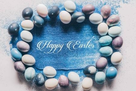 Photo for Top view of painted easter eggs and happy easter lettering on blue sand on white surface - Royalty Free Image