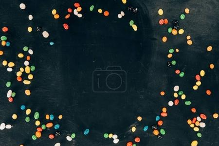 top view of arranged colorful sweets on black tabletop