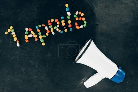 flat lay with loudspeaker and candies arranged in 1 aprils lettering on black tabletop
