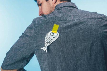 back view of man with fish on sticky tape on back, april fools day holiday concept