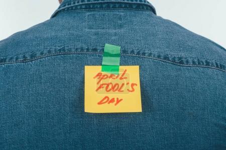 Photo pour Arrière de l'homme avec note sur un ruban adhésif avec avril imbéciles lettrage jour sur dos, concept de vacances jour poisson d'avril - image libre de droit