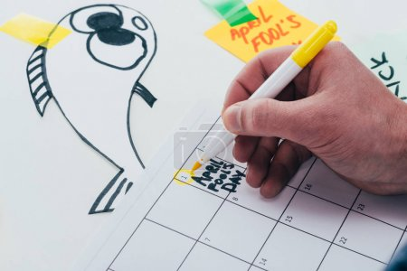 partial view of man making note on calendar isolated on grey, april fools day concept