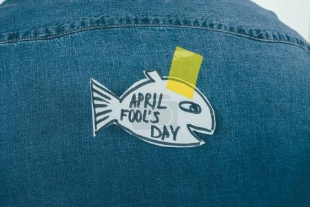 close up view of paper made fish with sticky tape on jeans shirt, april fools day concept