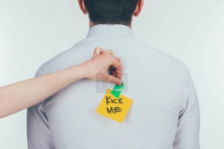 cropped shot of woman putting note with kick me lettering on males back, 1 april holiday concept