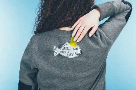 back view of woman with hand drawn fish on back, april fools day concept