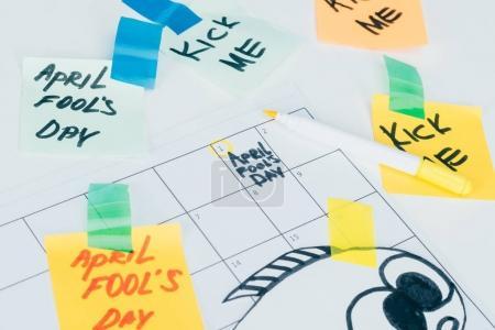 Photo pour Gros plan de vue du calendrier avec avril imbéciles lettrage jour isolé sur la surface grise, concept de vacances jour poisson d'avril - image libre de droit