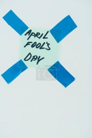 close up view of note with april fools day lettering and sticky tapes isolated on grey, april fools day concept
