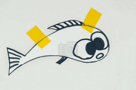 close up view of hand drawn fish with sticky tapes isolated on grey, april fools day holiday concept