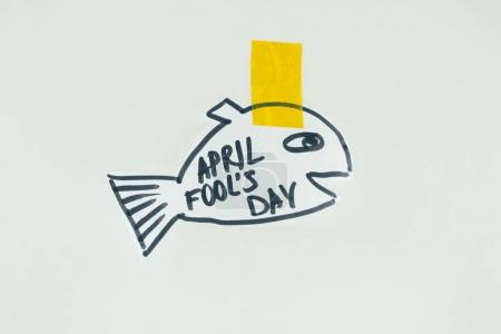 close up view of hand drawn fish with april fools day lettering and sticky tape isolated on grey, april fools day holiday concept