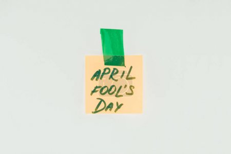 close up view of note with april fools day lettering and sticky tape isolated on grey, april fools day concept
