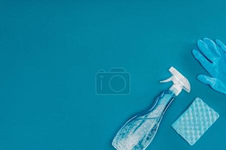 top view of spray bottle and rubber glove with washing sponge isolated on blue