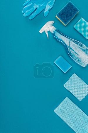 top view of washing sponges and spray bottle for cleaning isolated on blue
