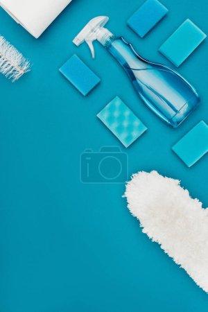 Photo pour Vue de dessus du vaporisateur, laver les éponges et brosse à épousseter isolé sur bleu - image libre de droit