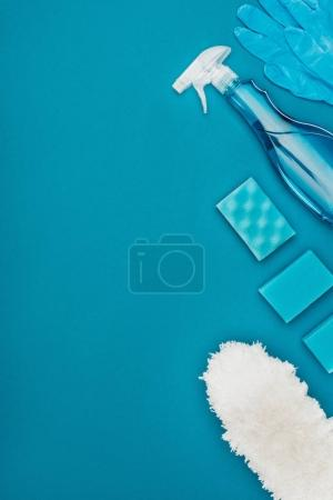 top view of rubber gloves and washing sponges for cleaning isolated on blue