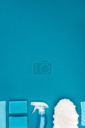 top view of washing sponges and cleaning supplies isolated on blue