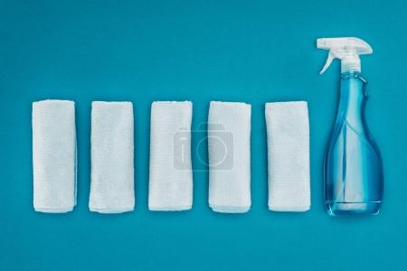 top view of row of rags and spray bottle isolated on blue