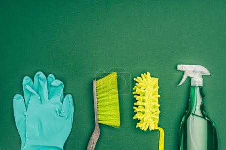 top view of rubber gloves and brushes isolated on green