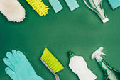top view of cleaning supplies isolated on green