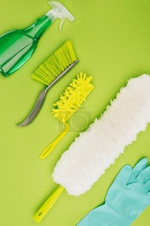 vista superior de diferentes cepillos de limpieza y guantes de goma aislados en verde claro