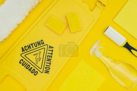 Photo for Top view of wet floor sign and cleaning supplies isolated on yellow - Royalty Free Image