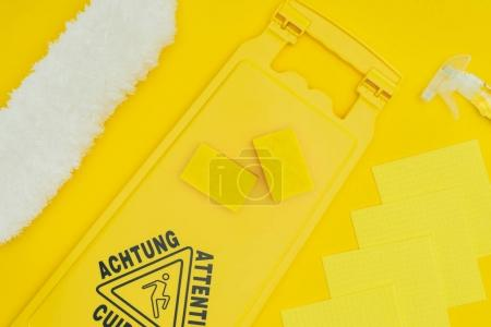 top view of wet floor sign and washing sponges isolated on yellow