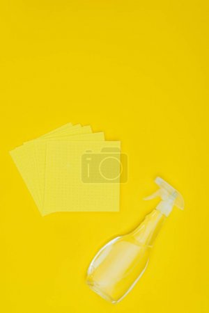 elevated view of yellow rags and spray bottle isolated on yellow